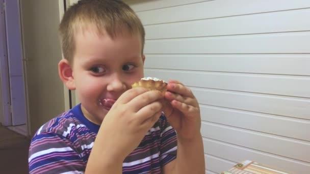 Roztomilý chlapec doma jíst chutné košíčky se šlehačkou a ovocem