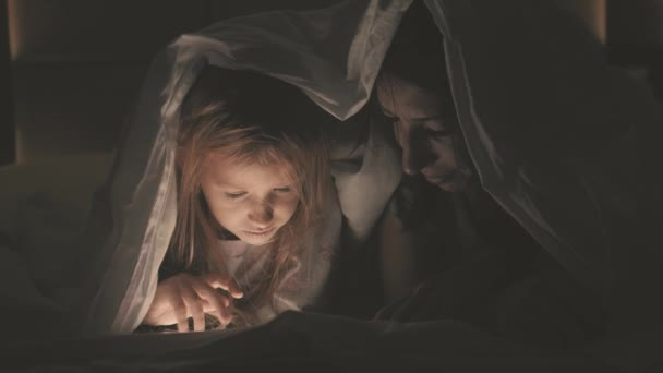 Young woman mom and her daughter watching interesting film together on tablet and laugh under the blanket. Funny mom and lovely child are having fun with tablet. Happy loving family.