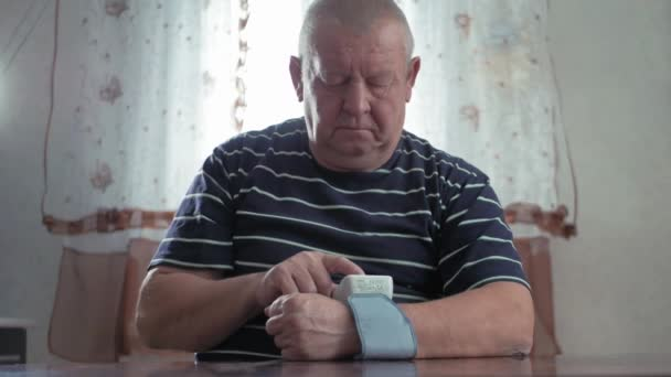 Senior man taking his blood pressure at home on the table. Men health check blood pressure.and heart rate with digital pressure gauge standard blood pressure test results .Health and Medical concept.