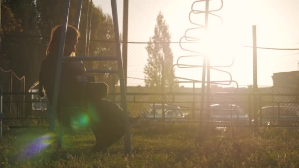 Bambino ragazzo e giovane madre oscillante a giochi per bambini nel parco. Bambino felice che hanno buon tempo allaperto.