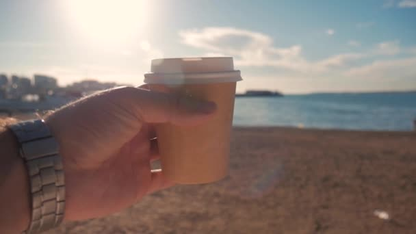 Tourist man holding a hot glass of coffee against the beach and blue sea. Travel and Tourism Concept.