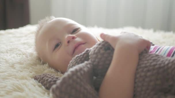 Szép kisfiú hugs egy plüss nyúl az otthoni beltéri. Kis baby boy játék a játék.