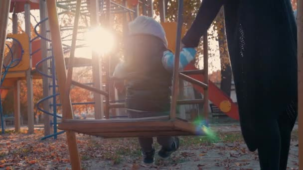 Baby boy swinging at children playground in park. Happy child having good time outdoors.
