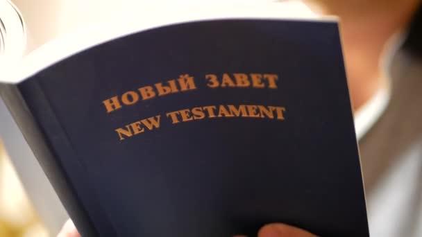 Az ember egy kézi könyvek flip segítségével olvasni. Közelről nyitott könyve essek oldalak. Biblia oldal közeli képe