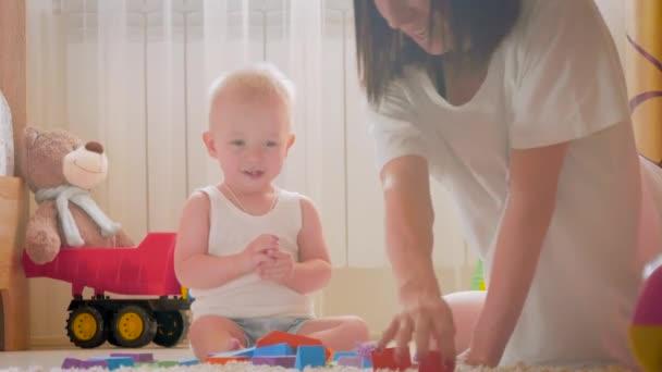 Matka a její dítě hrát s hračkami uvnitř. Procházení legrační chlapeček na podlahu doma. Matka a malý syn hraní s kostkami spolu doma. Vzdělávací hry pro děti.