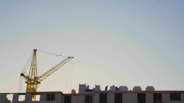 Jeřáb a budování staveniště při západu slunce. Silueta pracovníků na pozadí oblohy.