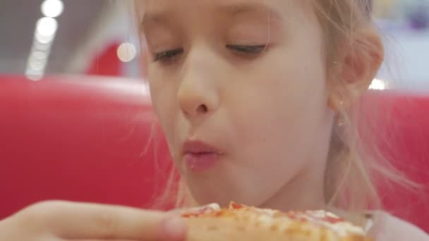 A young girl with plaits is eating a piece of pizza. Charming happy young girl laugh and biting off big slice of fresh made pizza. International food concept. Close up.