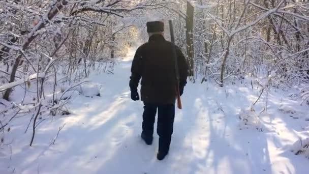 Hunter procházky v zasněžené zimní les. Zimní koníček, slunce, lov koncept.