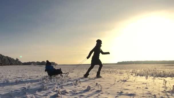 Little boy líbí jízda na saních. Matka sáně jeho roztomilé dítě. Zimní outdoor aktivity. Šťastná rodina baví venkovní