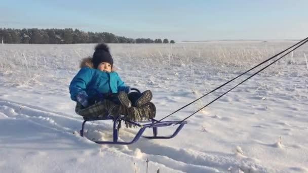 kleiner Junge genießt eine Schlittenfahrt. Baby auf dem Schlitten. Kinder spielen draußen im Schnee. Frohe Winterferien. Winterspaß.