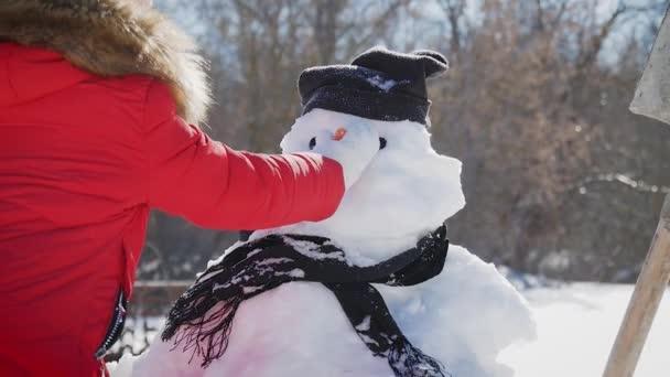 Lány beszúr egy orr a hóember. A gyermek játszik egy hóember. Téli boldog idő, hó gyerek.