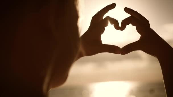 Mladá krásná dívka dělá srdce za ruce ve tvaru srdce rámující západ slunce při západu slunce nad oceánem. Emocionální koncept šťastného exkluzivního životního stylu, sdílení času, relaxace.