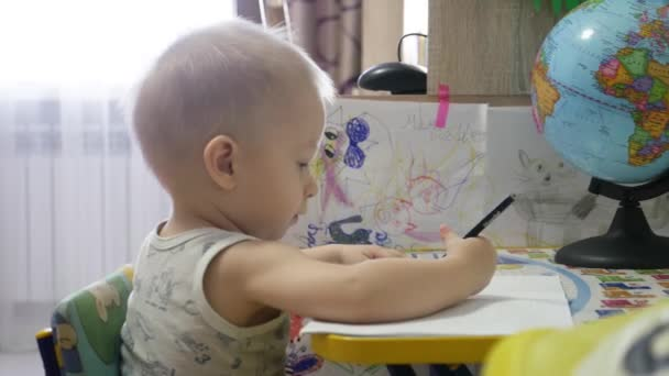 Cute kid boy painting at home, 1 year old toddler baby boy child painting with pencils, happy preschooler. Creative play for toddlers concept.