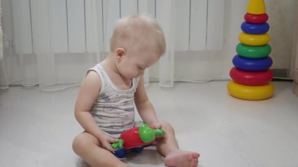 Little baby boy playing with colourful small blocks of a constructor in the room on the floor. Kid playing with colored blocks of a constructor on floor in children room.