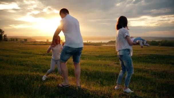 Šťastná rodina Matka otce a děti na louce na západ slunce. Mladá rodina spolu trávili čas venku v zeleni.