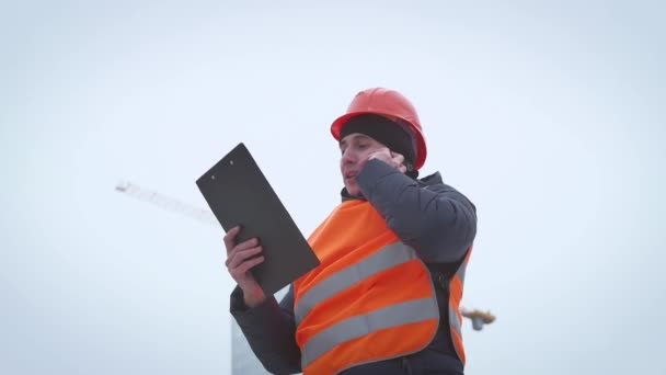 Young handsome engineer, architect, builder, businessman, wearing a helmet, in a construction vest, using the phone, building skyscraper background.