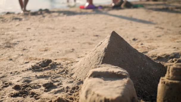 Sandcastles in shape of pyramids on a beach