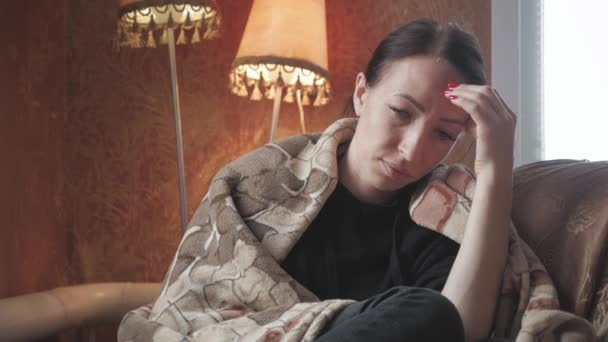 Depressziós szomorú nő holding vezetője, otthon a karosszékben ülő kezében. Életmód drámai portré vonzó és szomorú lány, szenvedés, szorongás válság és a depresszió probléma átgondolt és kétségbeesett.