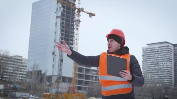 Business, Building, Papierkram und People Konzept - glücklicher Bauherr in Hardhat mit Klemmbrett auf der Baustelle. Ingenieure mit Bauplan auf der Baustelle.