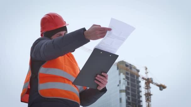 Obchodní, stavební, papírování a lidé koncept - šťastný builder v bezpečnostní přilba s schránky na staveništi. Stavební inženýr s plán na staveništi.
