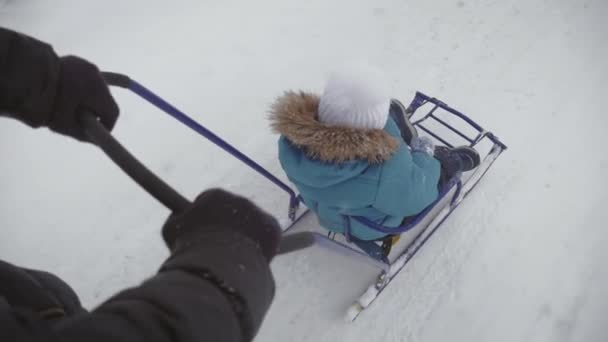 Little boy enjoying a sleigh ride. Mother sled his cute child. Family winter activities outdoors. Happy family having fun outdoor.