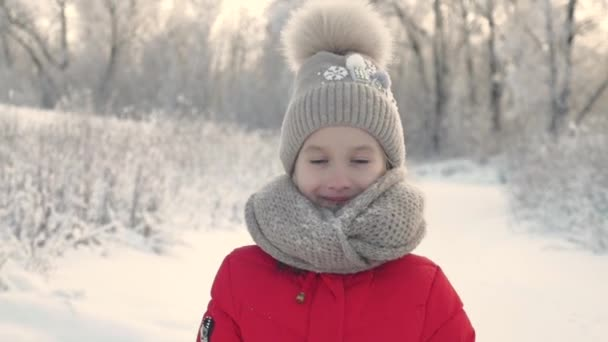 Portrait of a little girl in knit scarf and hat on a background of a snow park. Beautiful child girl in a park looking and being thoughtful during a cold winter day, outdoors.