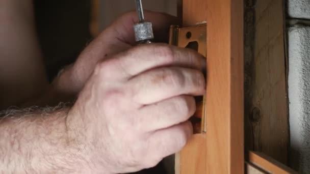 Close-up Zimmermann Prozess der Holztür Scharnier Installation. Tür Scharnier Einbau.