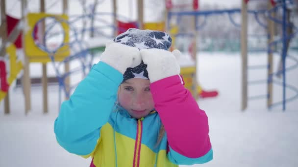 Little girl playing peek-a-boo with the camera at winter park. The concept of child joy and happiness.