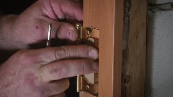 Close-up Zimmermann Prozess der Holztür Scharnier Installation. Tür Scharnier Einbau
