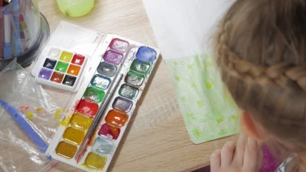 Tizenéves lány otthon részt vesz a kreativitás szobában egy asztalnál felhívja akvarell. Gyermek rajz felülnézet. Grafikát munkahelyi kreatív kiegészítők.