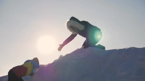 Silhouette of helping hand between mother and daughter. Two hikers on top of the mountain, a woman helps a girl to climb a snow mountain. Teamwork silhouette in winter mountains with sunlight.