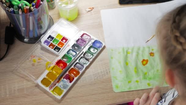 Teenager-Mädchen zu Hause beschäftigt sich mit Kreativität, zieht Aquarell an einem Tisch im Zimmer. Kind Zeichnung Draufsicht. Kunstwerk-Arbeitsplatz mit kreativen Accessoires.