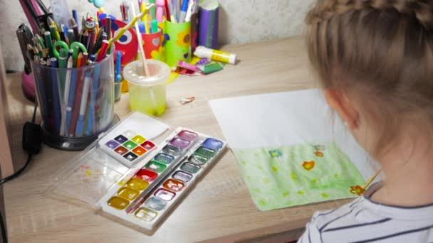 Tizenéves lány otthon részt vesz a kreativitás szobában egy asztalnál felhívja akvarell. Gyermek rajz felülnézet. Grafikát munkahelyi kreatív kiegészítők