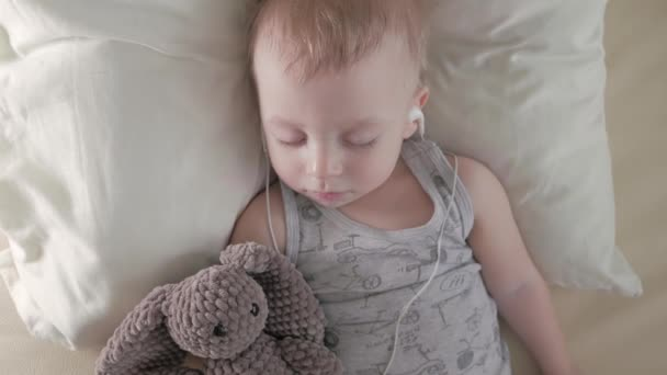 süßer kleiner Junge mit Kopfhörern schläft mit Teddybär.