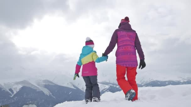 Mother and daughter enjoying journey. Happy family in winter clothing at the ski resort, winter time, watching at mountains in front of them. Frost winter season.
