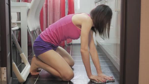 junges Mädchen beim Fußbodenputzen zu Hause. Frauenhaushaltskonzept.