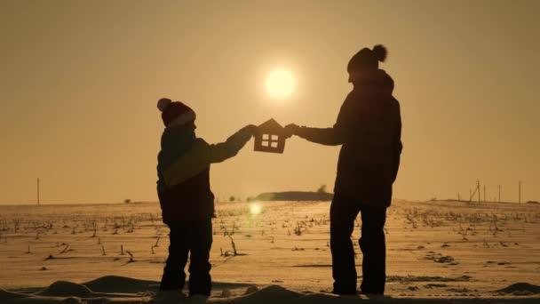 Silueta happy matka a dcera s dům snů. Papírové dům jako symbol. Koncepce rodinné štěstí.