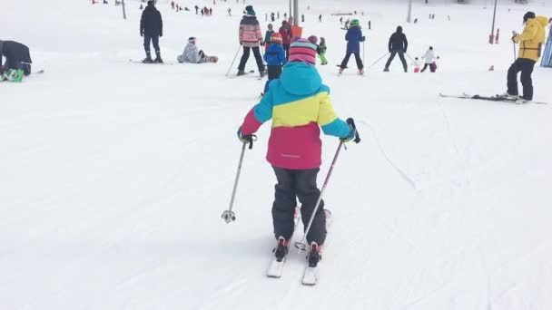 Archyz. Rusko - 25 ledna 2019: Aktivní dívka lyžování v horách. Lyžařský závod pro malé děti. Malý lyžař racing v sněhu.