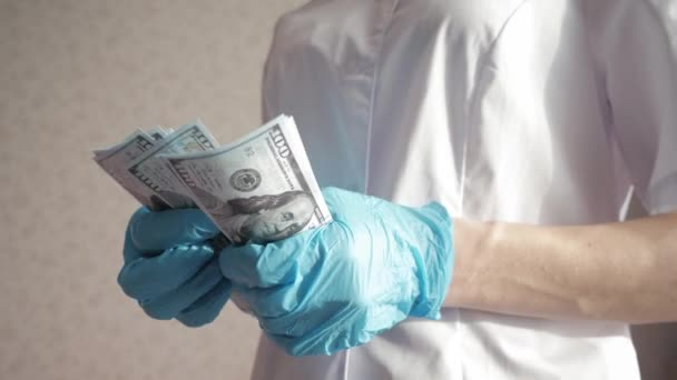 Doctor in uniform and blue gloves recounts money, the concept of giving take for medical services. Corrupted medical doctor counting money. Doctor accepting bribe and counting dollar bills close-up.