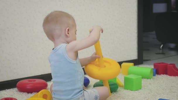 Concetto di infanzia, bambini e persone - neonato bello giocare con i giocattoli a casa.