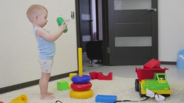 Gyermekkori, a gyerekek és az emberek koncepció - szép baba fiú játék-val toys otthon.