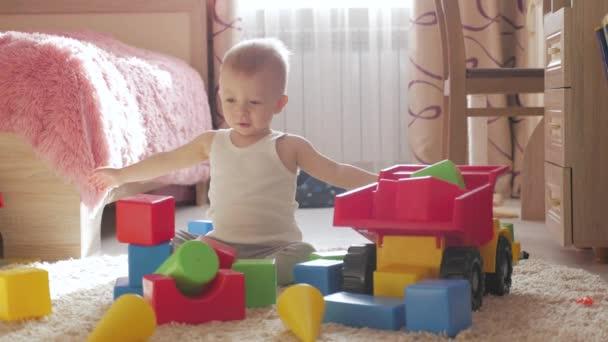 Mladý chlapec hraje s stavebních bloků sedí na podlaze doma. Dětské hry na podlahu s Vzdělávací hračky.