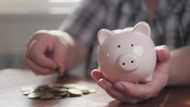 Woman putting coin in piggy bank, saving money concept. Future needs loan education or mortgage credit spend vacation of dream effective buying financial risk.