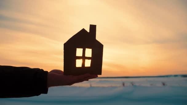 Silueta ruku s domem papíru při západu slunce pozadí.