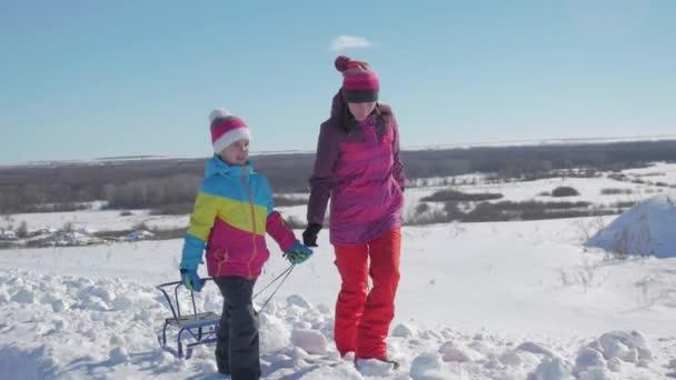 glückliche Familie Mutter und Kind Tochter auf einem Winterspaziergang im Freien Rodeln. schöne Familie mit Mutter und Kindern genießen sonnigen Wintertag im Freien Spaß beim Rodeln, Lifestyle.