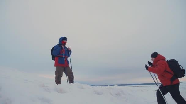 Lezec pomoci kolega stoupání, muž s batohem natáhl pomocnou ruku svého přítele. Tři horolezci na svahu sníh v horách, lezení na vrchol hory v zimě.