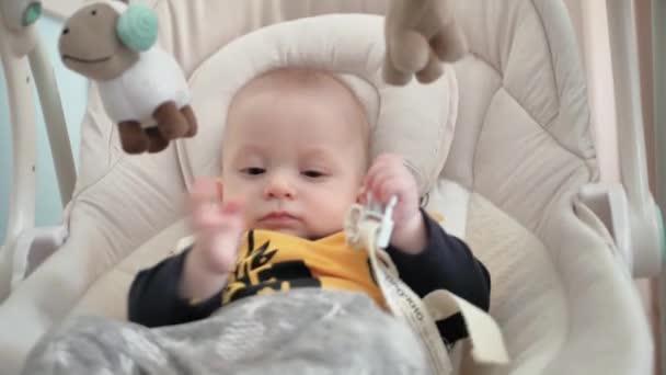 Novorozený chlapec leží na houpačce automatické elektrické křeslo a těší hračky.