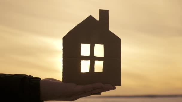 Silhouette Hand mit Papierhaus bei Sonnenuntergang Hintergrund.
