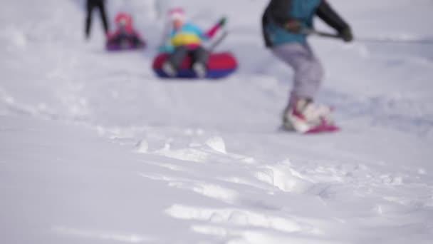Lyžař lyžování a lidé na snowboardy ride po svahu na lyžařské středisko v zimě hory.