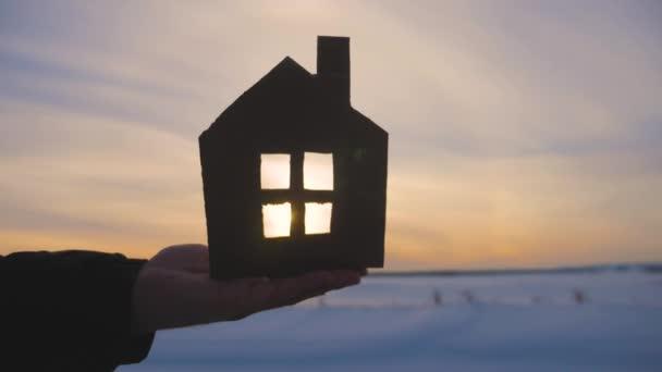 Sziluettjét kézzel papír house naplementében háttér.